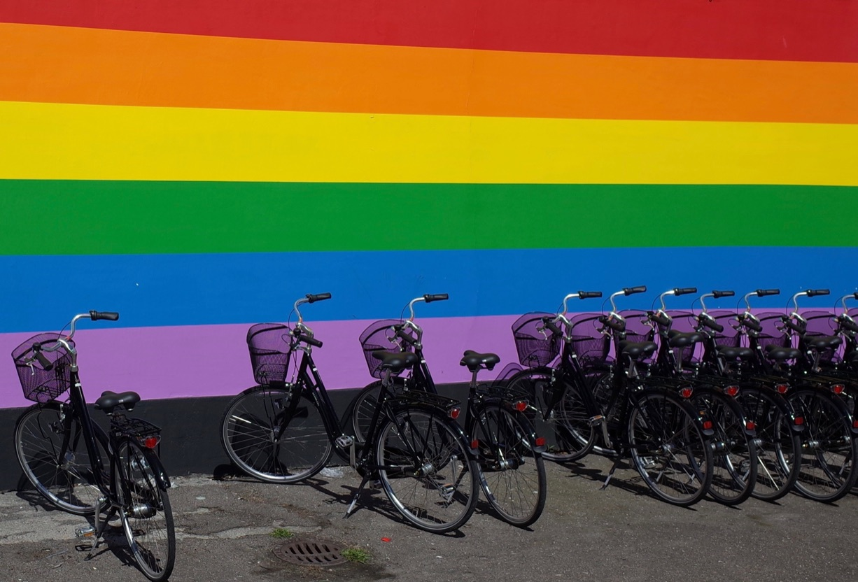 A row of bikes parked in front of a rainbow striped wall