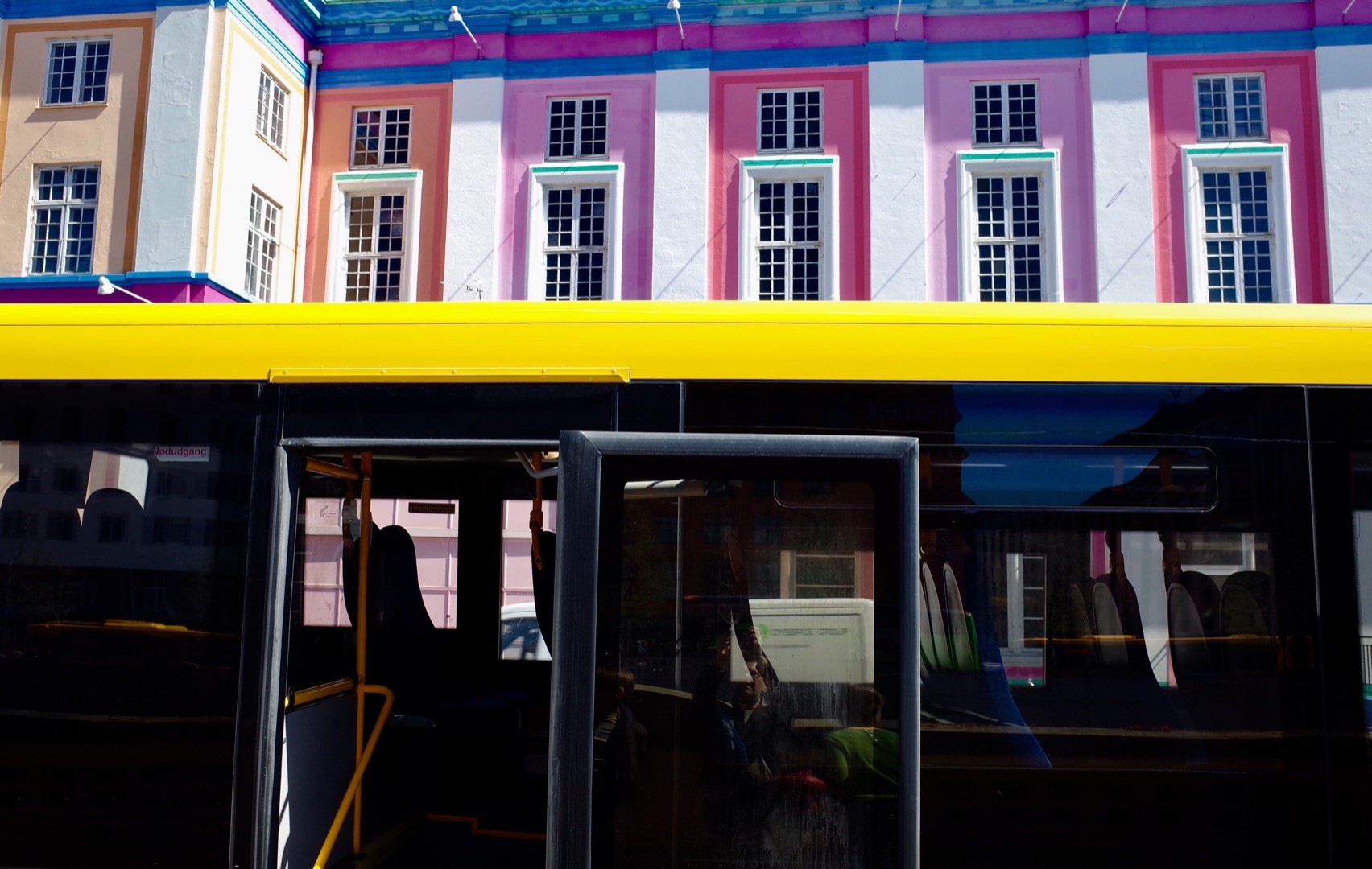 A yellow bus and brightly decorated architecture