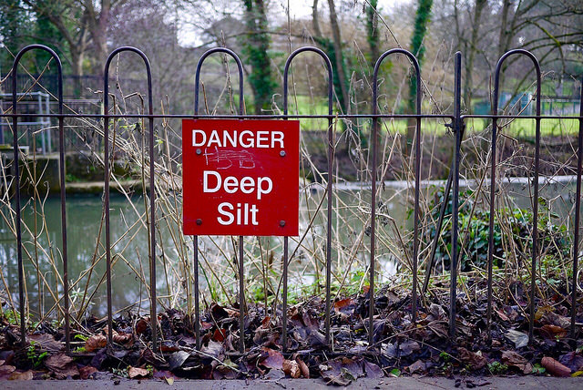A photo of a sign in front of a river. The sign reads 'Danger: deep silt'.