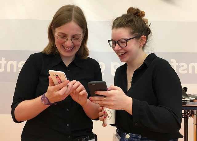 photo of 2 people looking at something on a phone and smiling