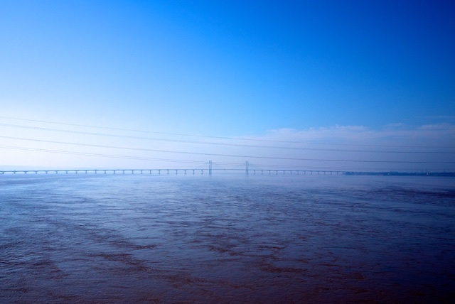 A photo of the Severn Bridge in the distance, between a blue sky above and the blue estuary below