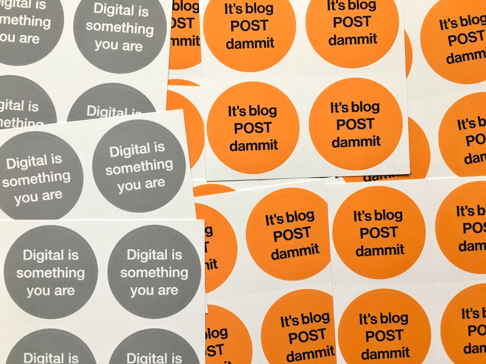 Stickers that say 'It's blog POST dammit' and 'Digital is something you are'